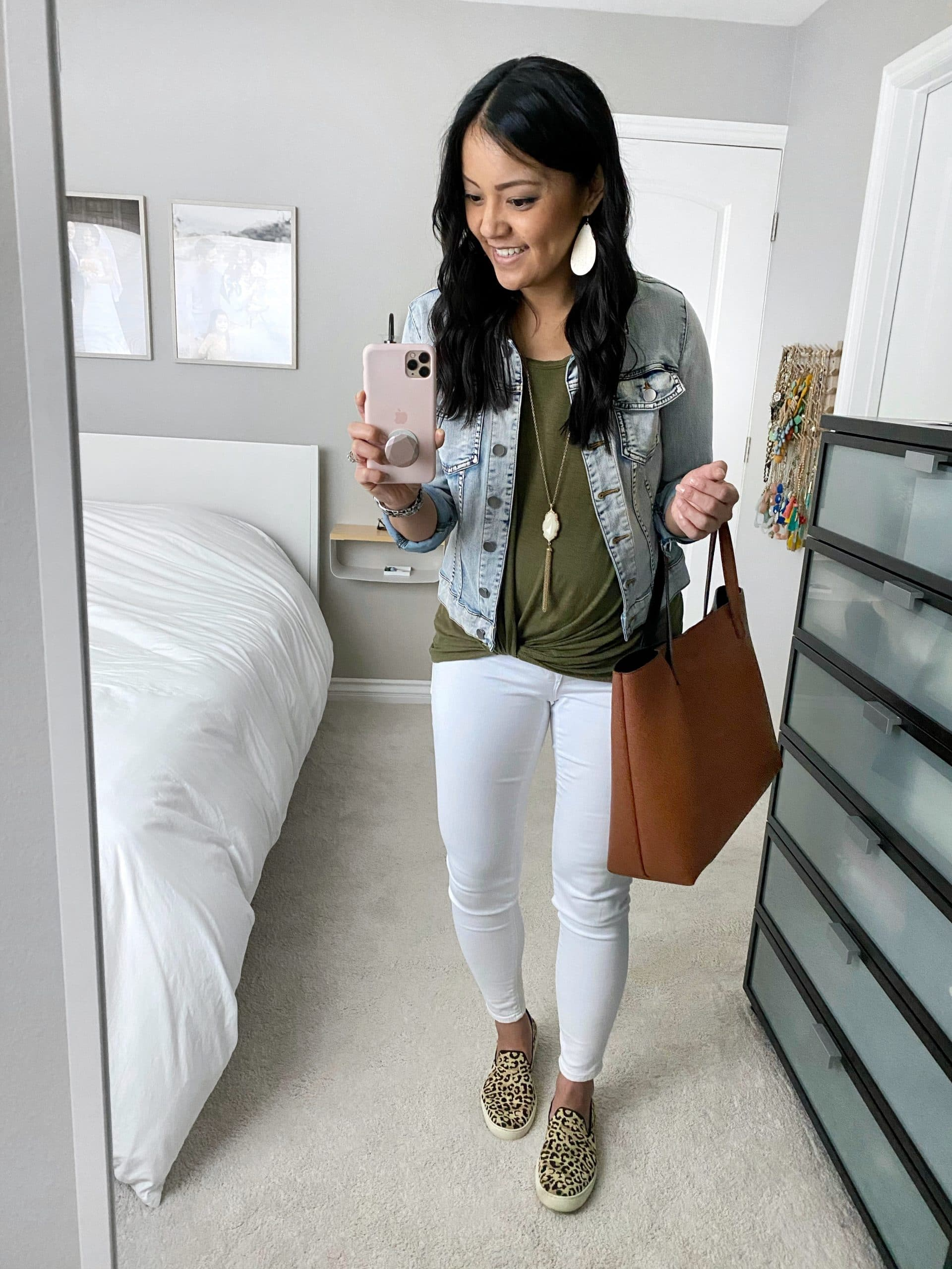 Casual Spring Outfit: olive twist front tee + denim jacket + white skinny jeans + leopard slip-on sneakers + cognac tote + long gold fringe pendant necklace + white leather earrings