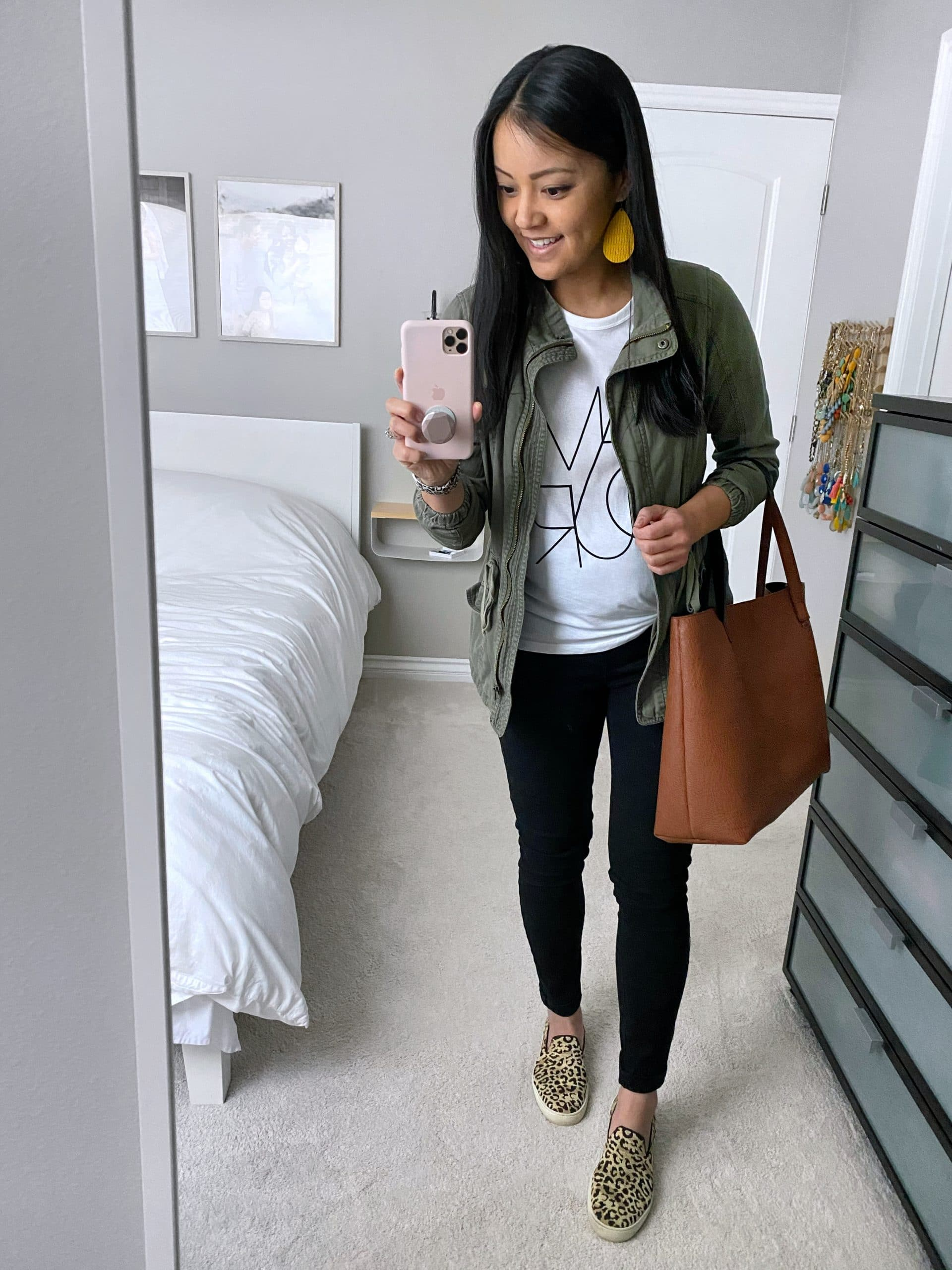 Casual Spring Outfit: white graphic tee + utility jacket + black skinny jeans + leopard slip-on sneakers + cognac tote + yellow leather earrings