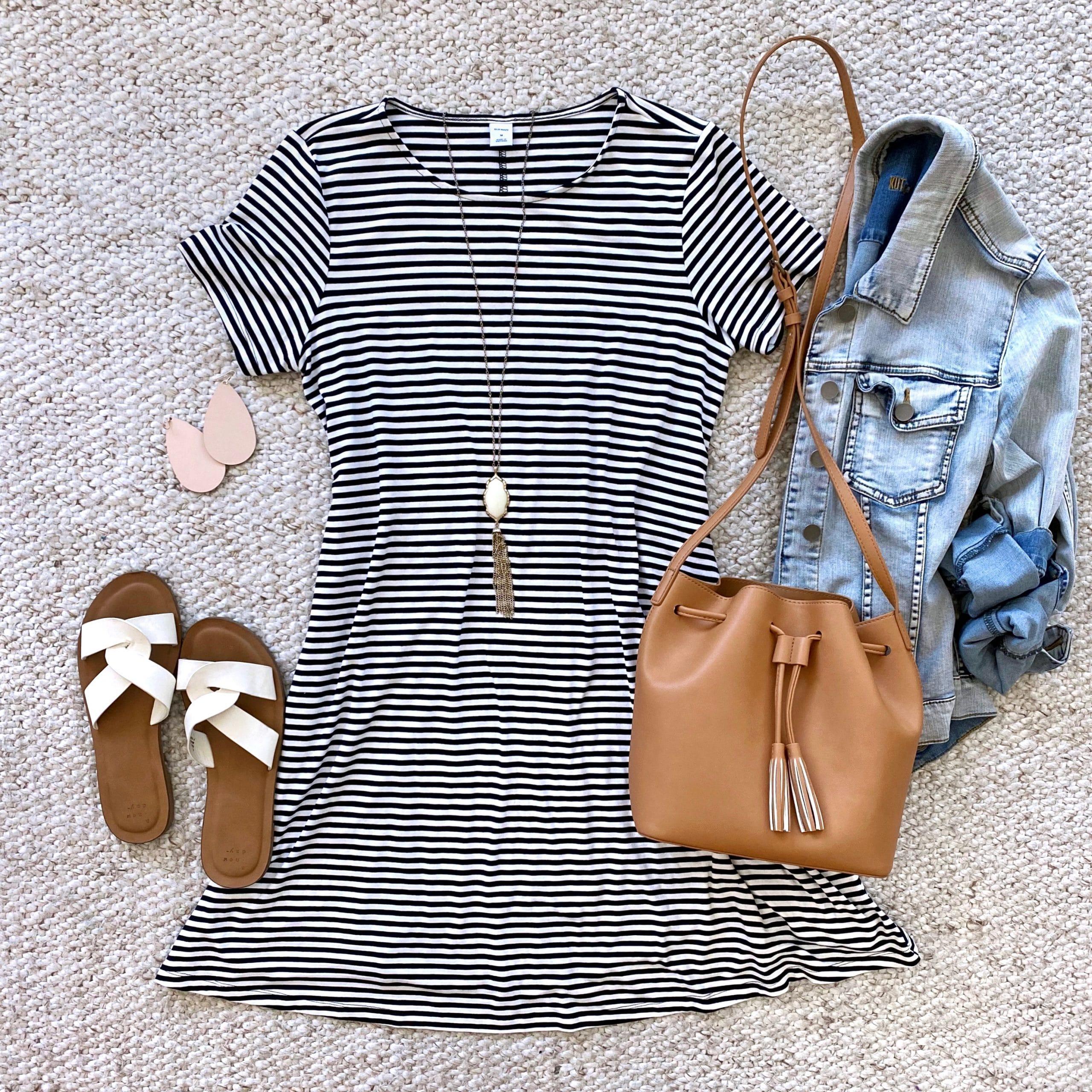 Casual Spring Outfit: striped swing dress + denim jacket + white slide sandals + tan drawstring crossbody bag + long gold fringe pendant necklace + blush leather earrings