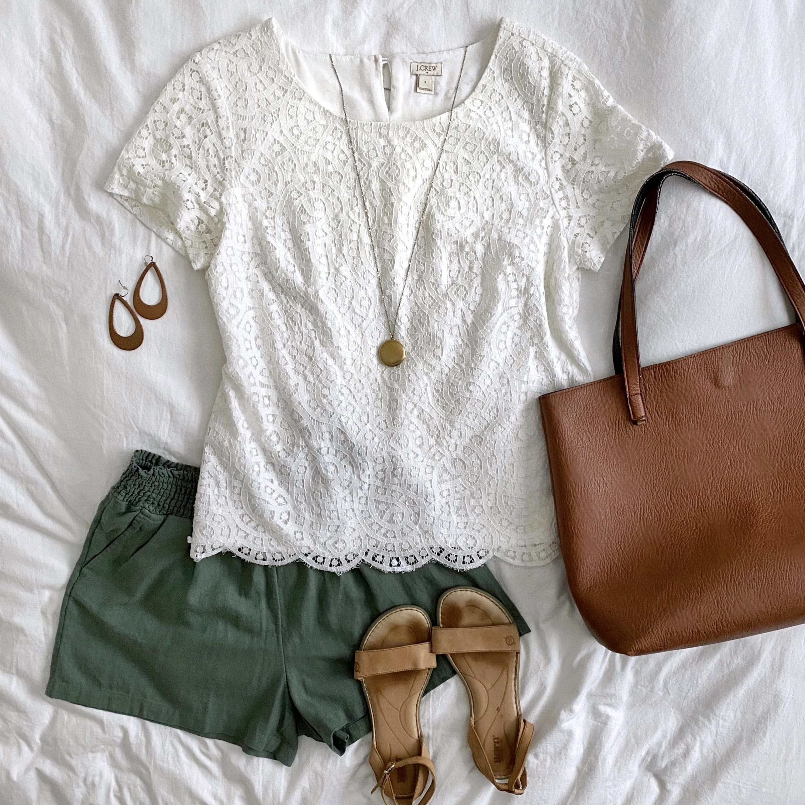 Summer Shorts Outfit: white lace top + olive linen shorts + tan ankle strap sandals + cognac tote + long gold disc pendant necklace + tan leather cutout earrings