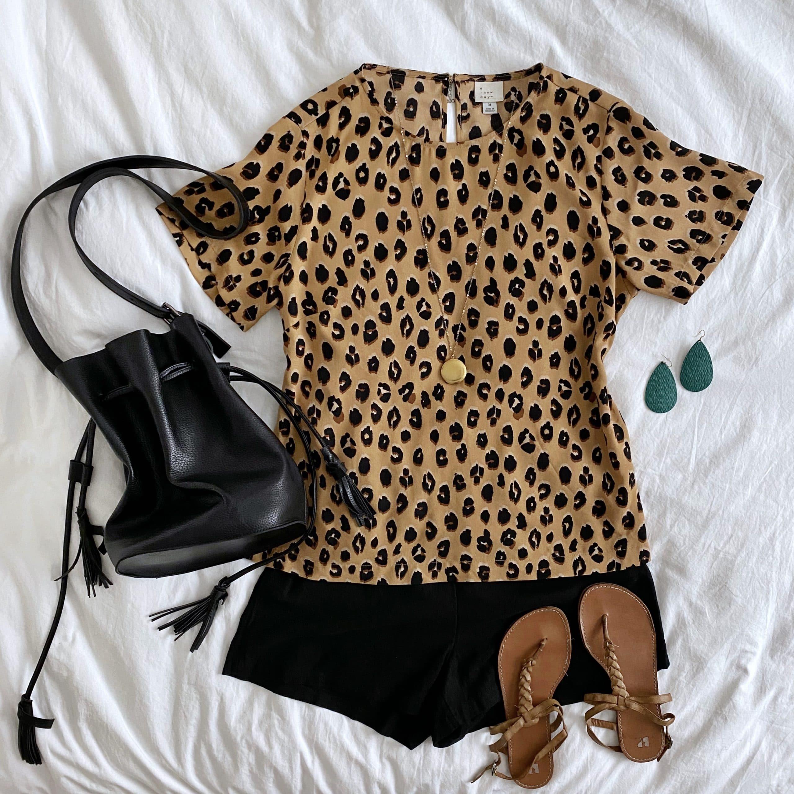 Summer Shorts Outfit: leopard short sleeve blouse + black linen shorts + tan braided sandals + gold disc pendant necklace + black drawstring crossbody bag