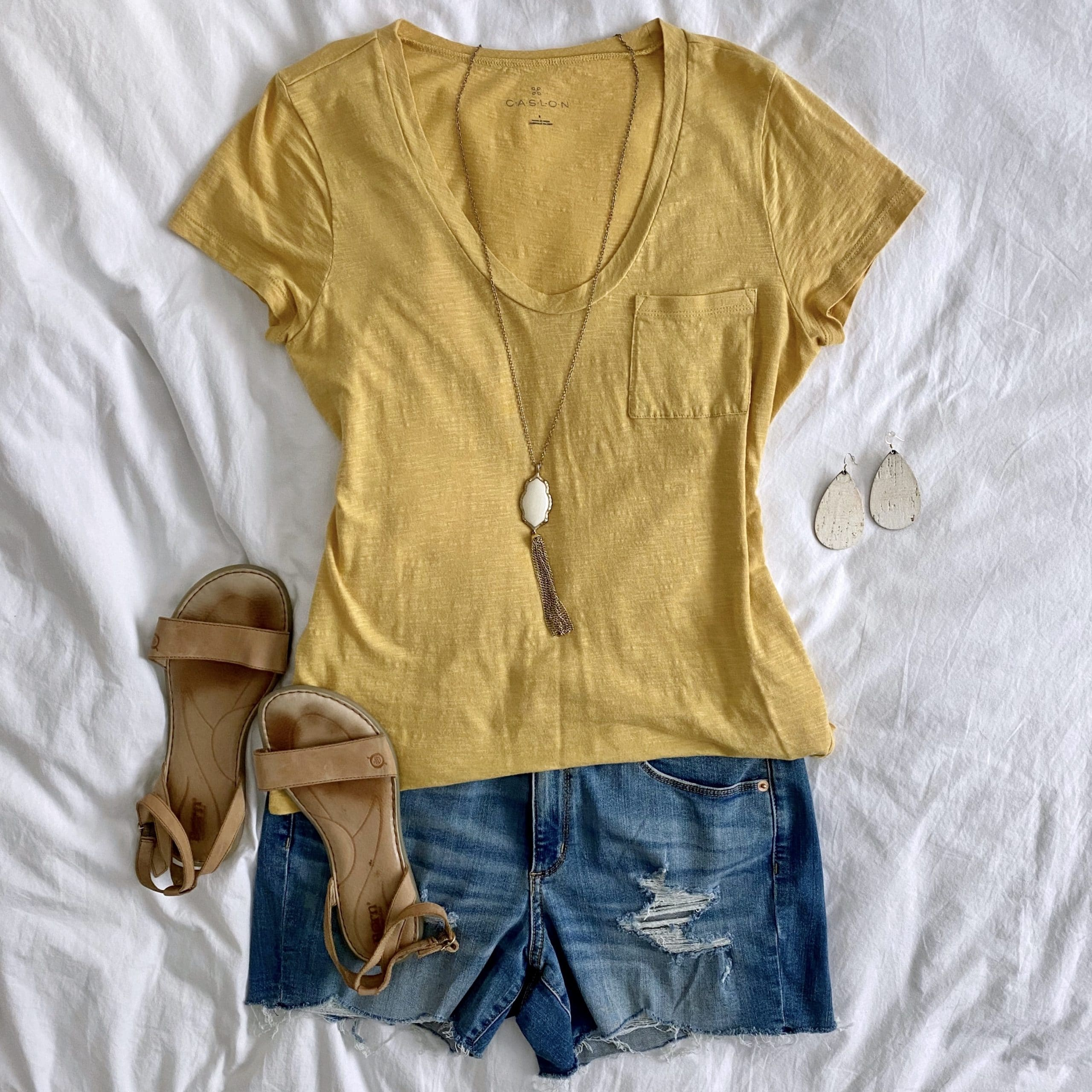 Summer Shorts Outfit: mustard tee + distressed jean shorts + tan leather sandals + white and gold tassel pendant necklace + white leather earrings