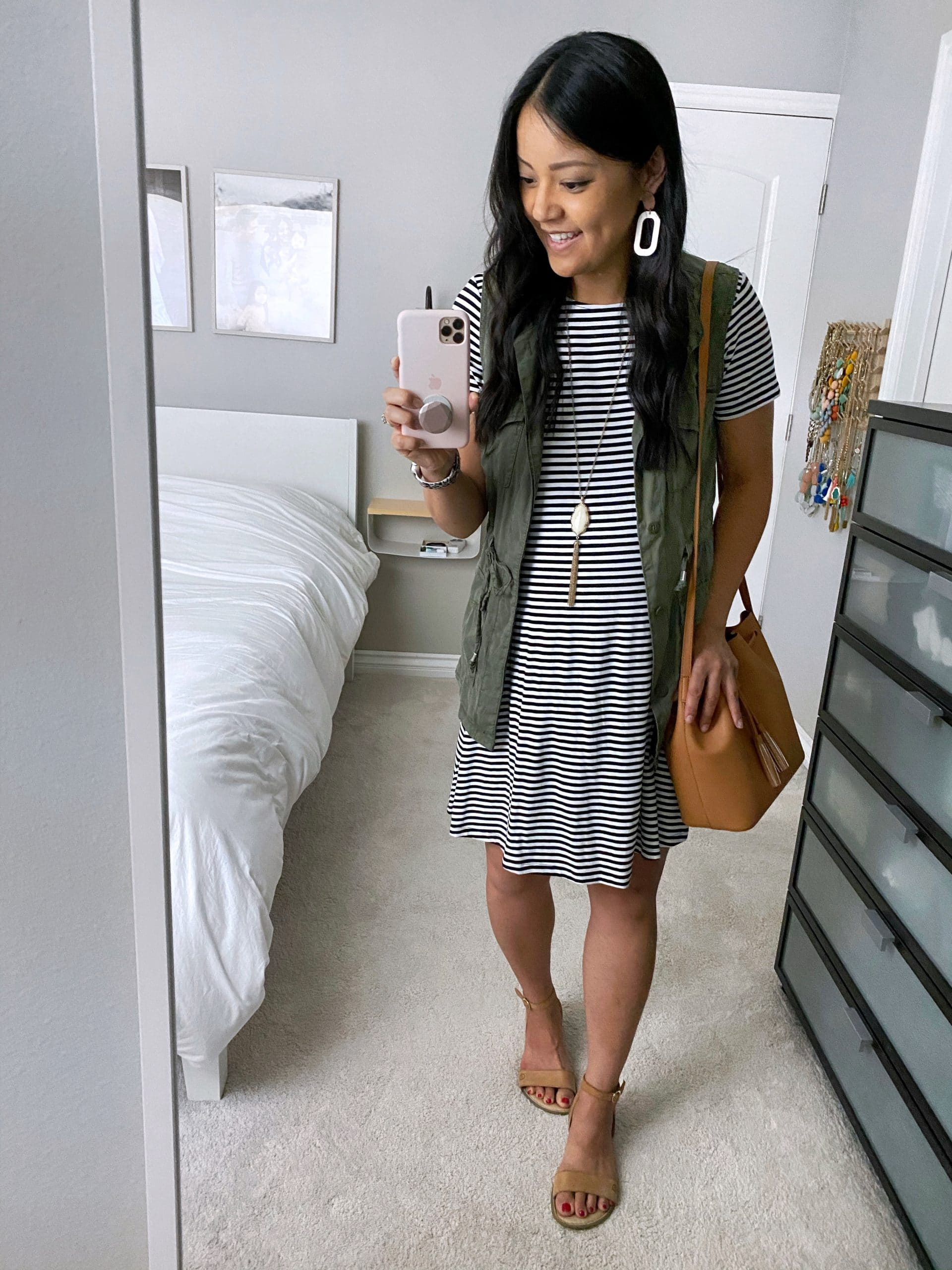 Striped Dress Outfit: black and white striped swing dress + utility vest + tan born sandals + tan drawstring crossbody bag + long gold and white tassel pendant necklace + white cutout leather earrings
