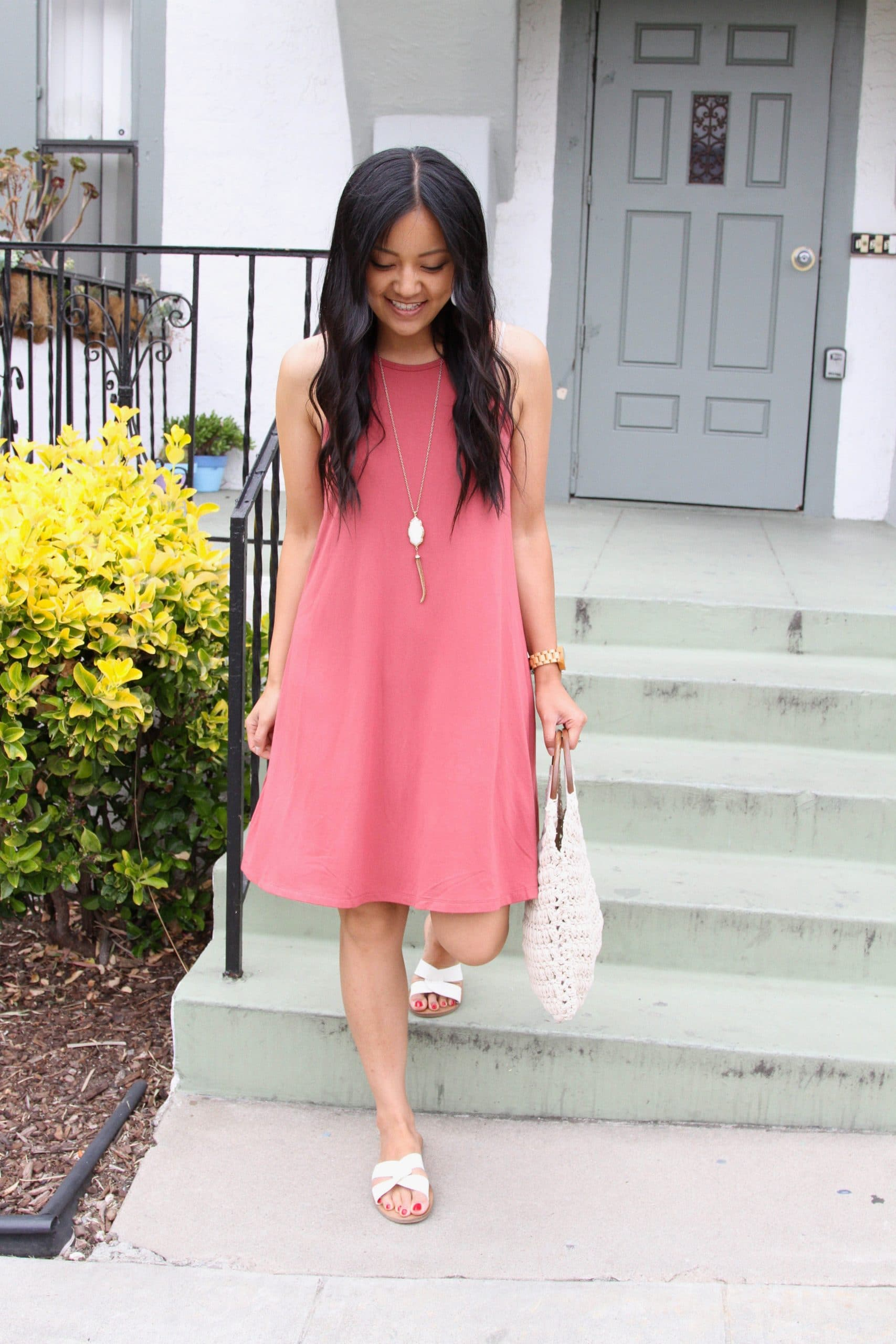 Casual Summer Dress Outfit: sleevelss pink swing dress + white slide sandals + white crochet bag + long gold fringe pendant necklace + white leather earrings