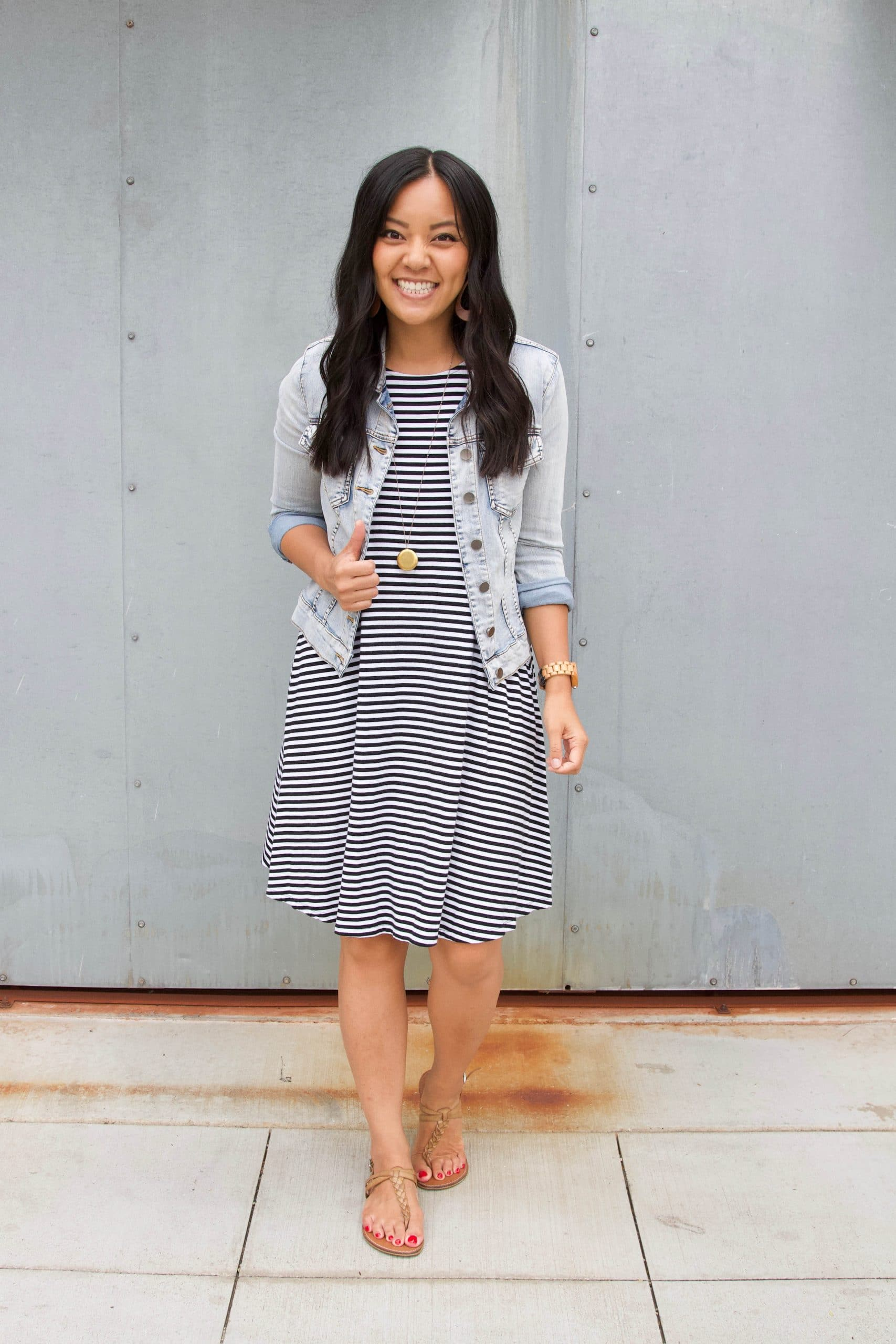 Striped Dress Outfit: black and white striped swing dress + denim jacket + tan thong sandals + long gold disc pendant necklace + tan leather earrings