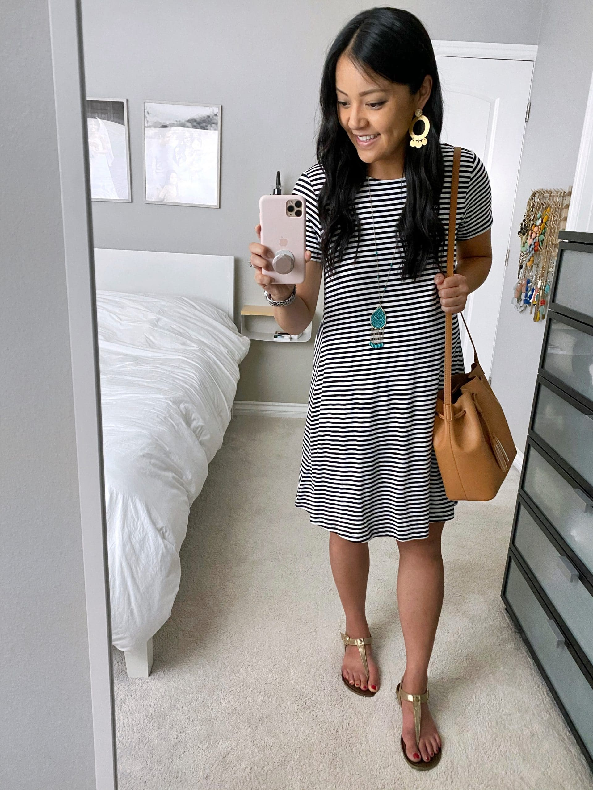 Striped Dress Outfit: black and white striped swing dress + gold thong sandals + tan drawstring crossbody bag + long turquoise pendant necklace + gold leather earrings