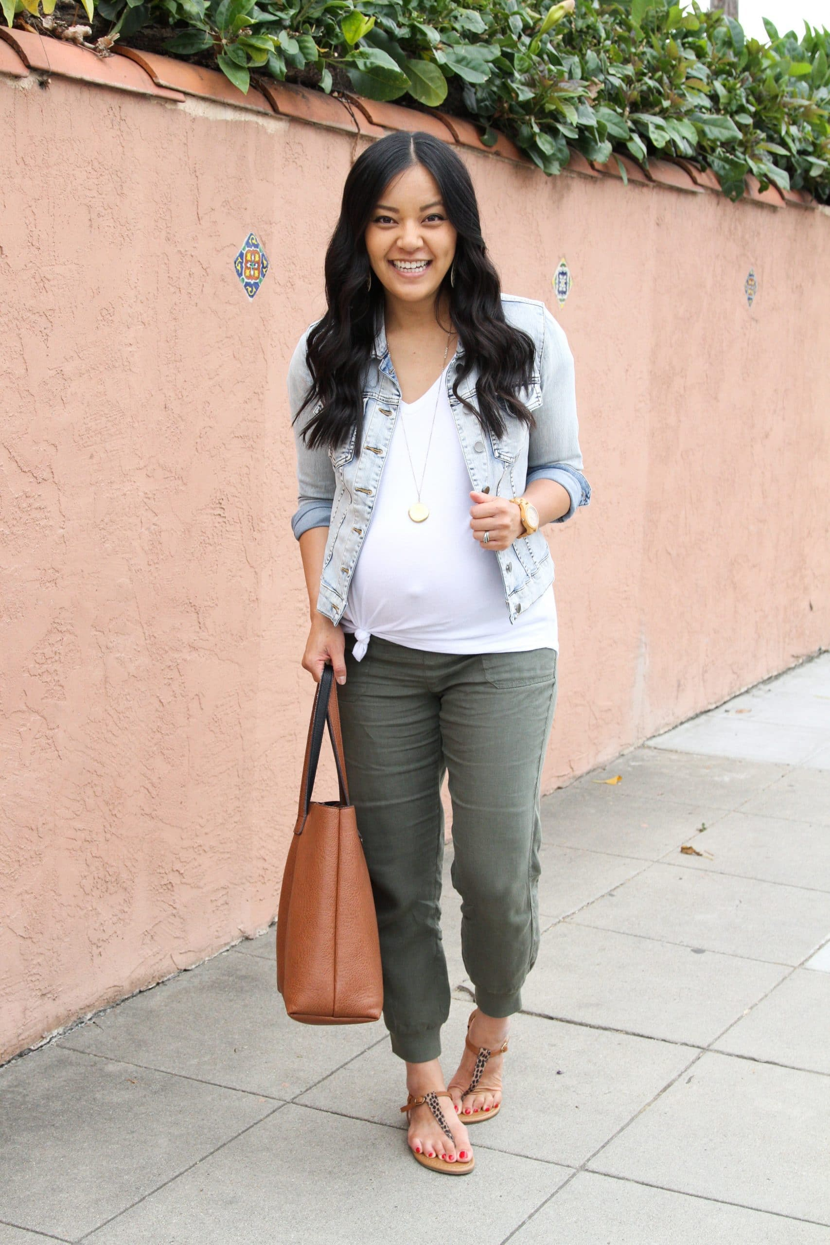Casual Summer Outfit: white v-neck tee + denim jacket + olive linen joggers + leopard thong sandals + cognac tote + long gold disc pendant necklace