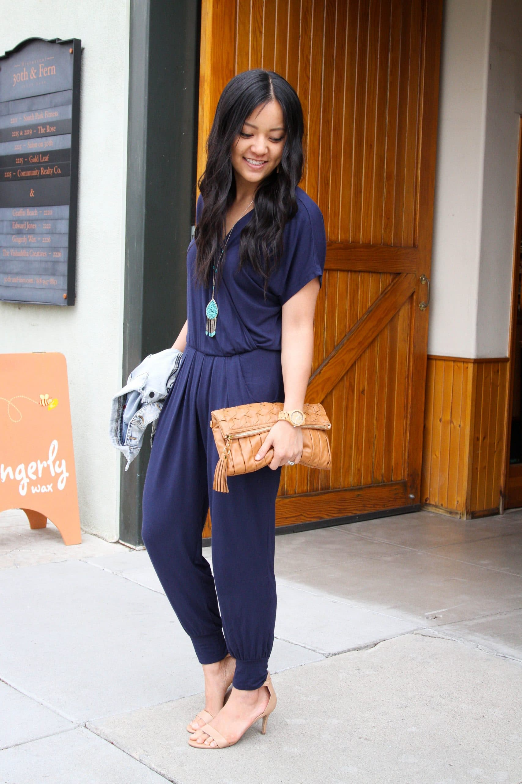 Dressy Casual Summer Outfit: denim jacket + navy short sleeve jumpsuit + camel leather clutch + nude heels + long turquoise pendant necklace