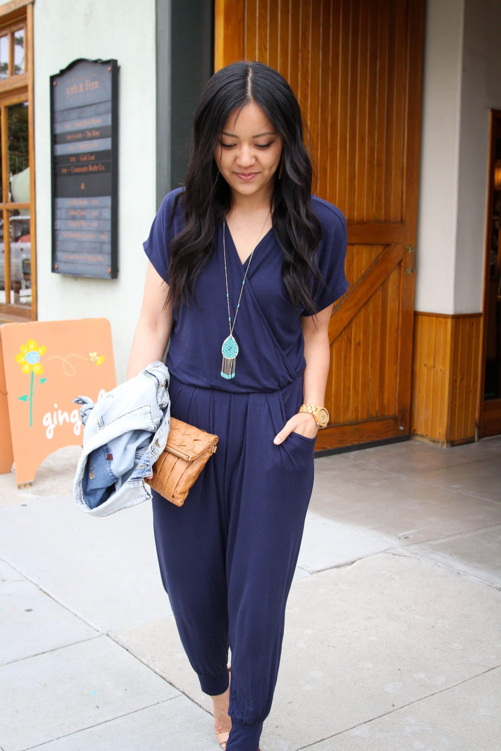 Dressy Casual Summer Outfit: navy short sleeve jumpsuit + denim jacket + camel leather clutch + nude heels + long turquoise pendant necklace