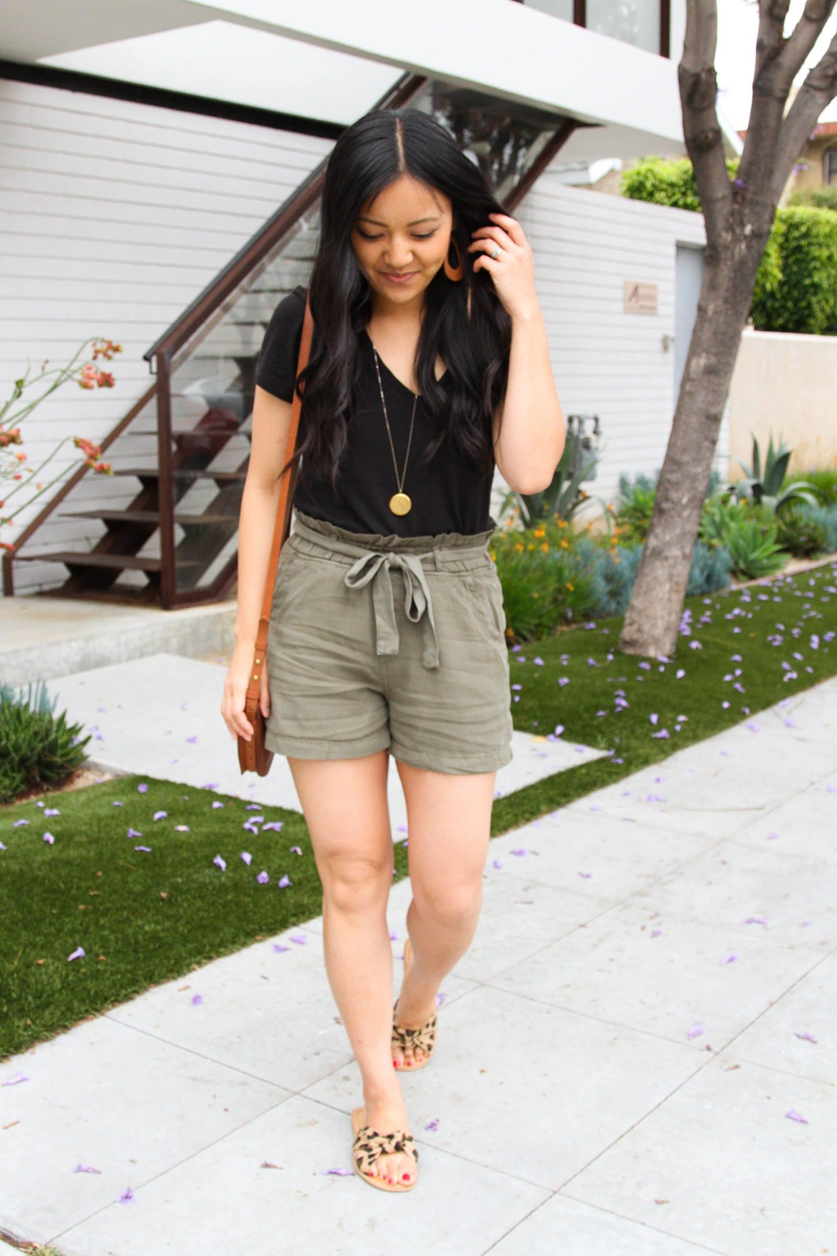 Summer Shorts Outfit: black v-neck tee + olive paper bag shorts + leopard slip-on sandals + cognac crossbody bag + long gold disc pendant necklace + tan leather earrings