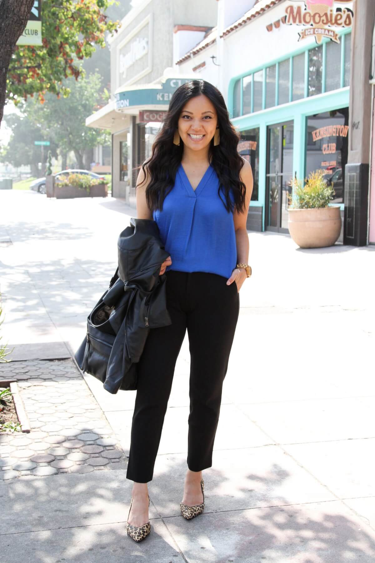 Business Casual Outfit: blue sleeveless blouse + black moto jacket + black ankle pants + leopard pumps + black hobo bag + tan leather earrings