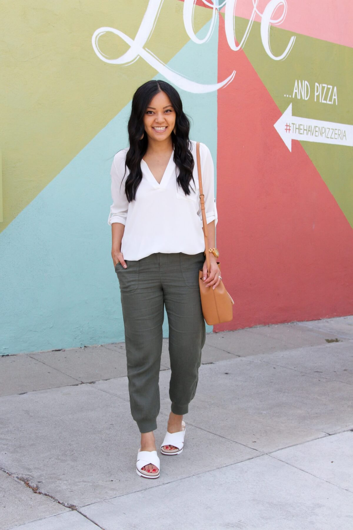 Summer Linen Pants Outfit: white v-neck tunic + olive linen joggers + white slide sandals + tan crossbody bag + tan leather earrings