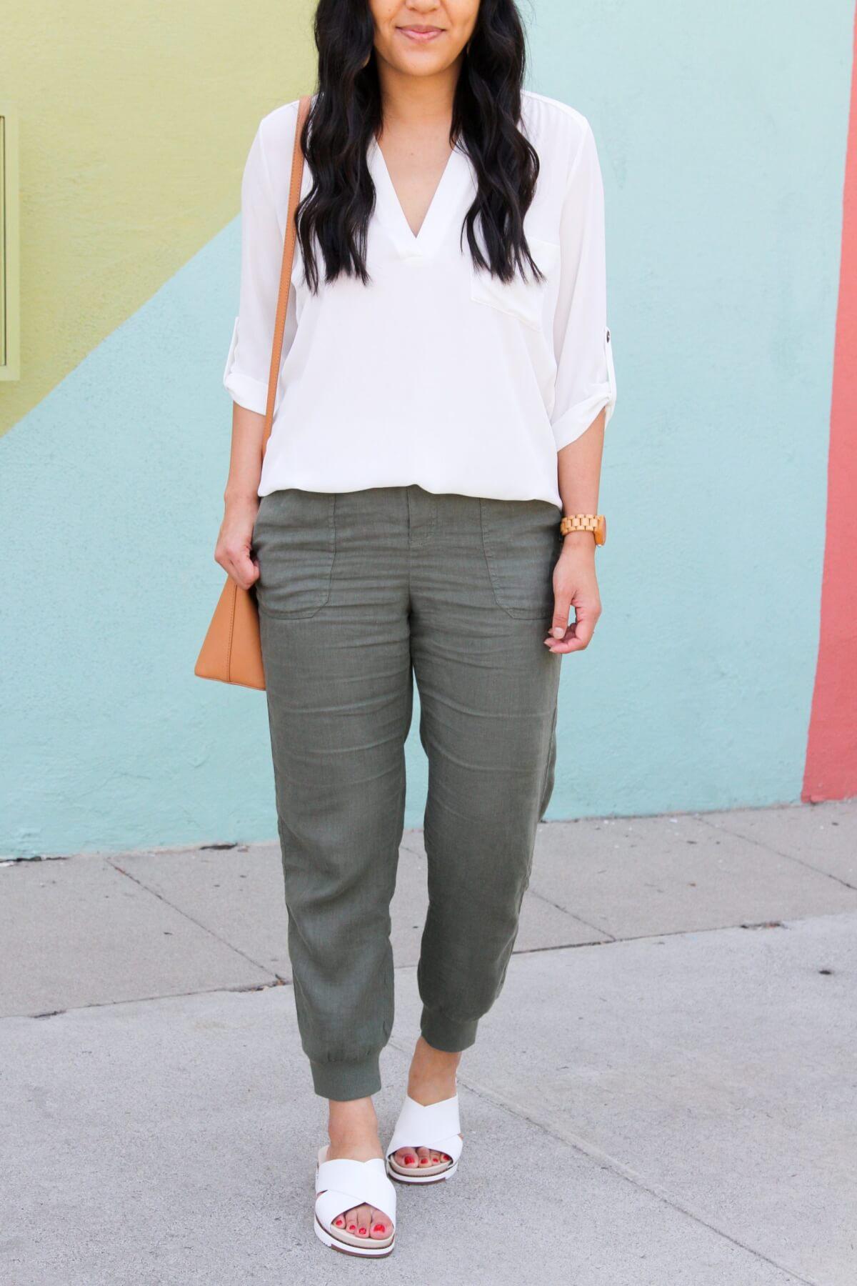 Summer Linen Pants Outfit:  white v-neck tunic + olive linen joggers + tan crossbody bag + white slide sandals + tan leather earrings