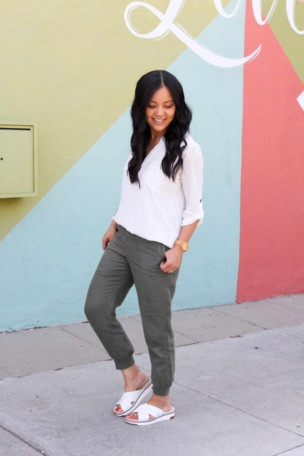 Summer Linen Pants Outfit: olive linen joggers + white v-neck tunic + tan crossbody bag + white slide sandals + tan leather earrings