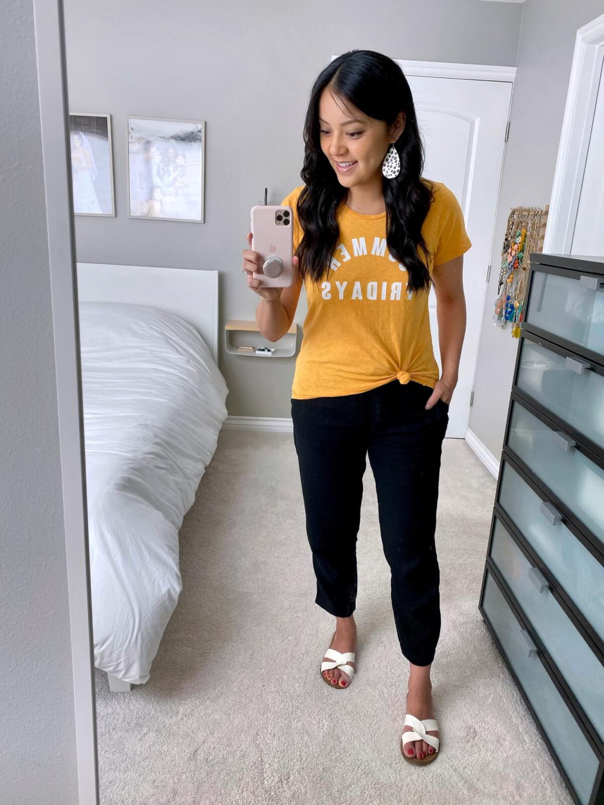 Casual Linen Pants Outfit: yellow graphic tee + black linen pants + white slide sandals + spotted leather earrings