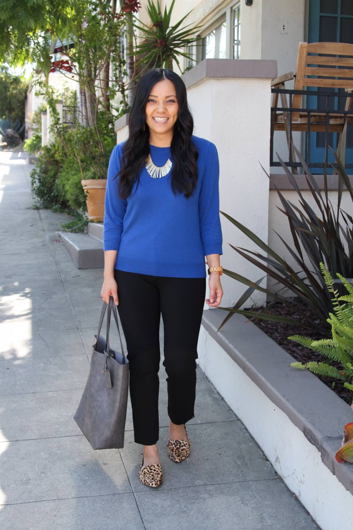 Business Casual Fall Outfit: blue pullover sweater + black pants + leopard loafers + grey tote + gold fringe statement necklace + tan leather earrings