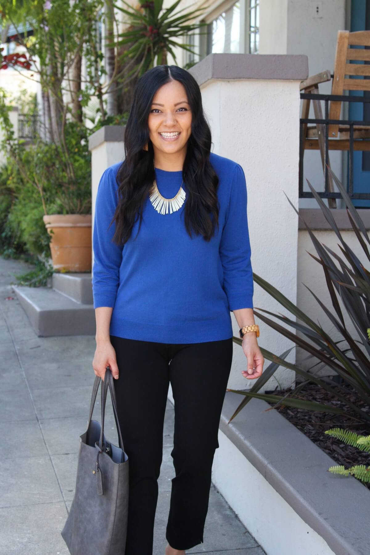 Business Casual Fall Outfit: blue pullover sweater + black pants + grey tote + leopard loafers + gold fringe statement necklace + tan leather earrings