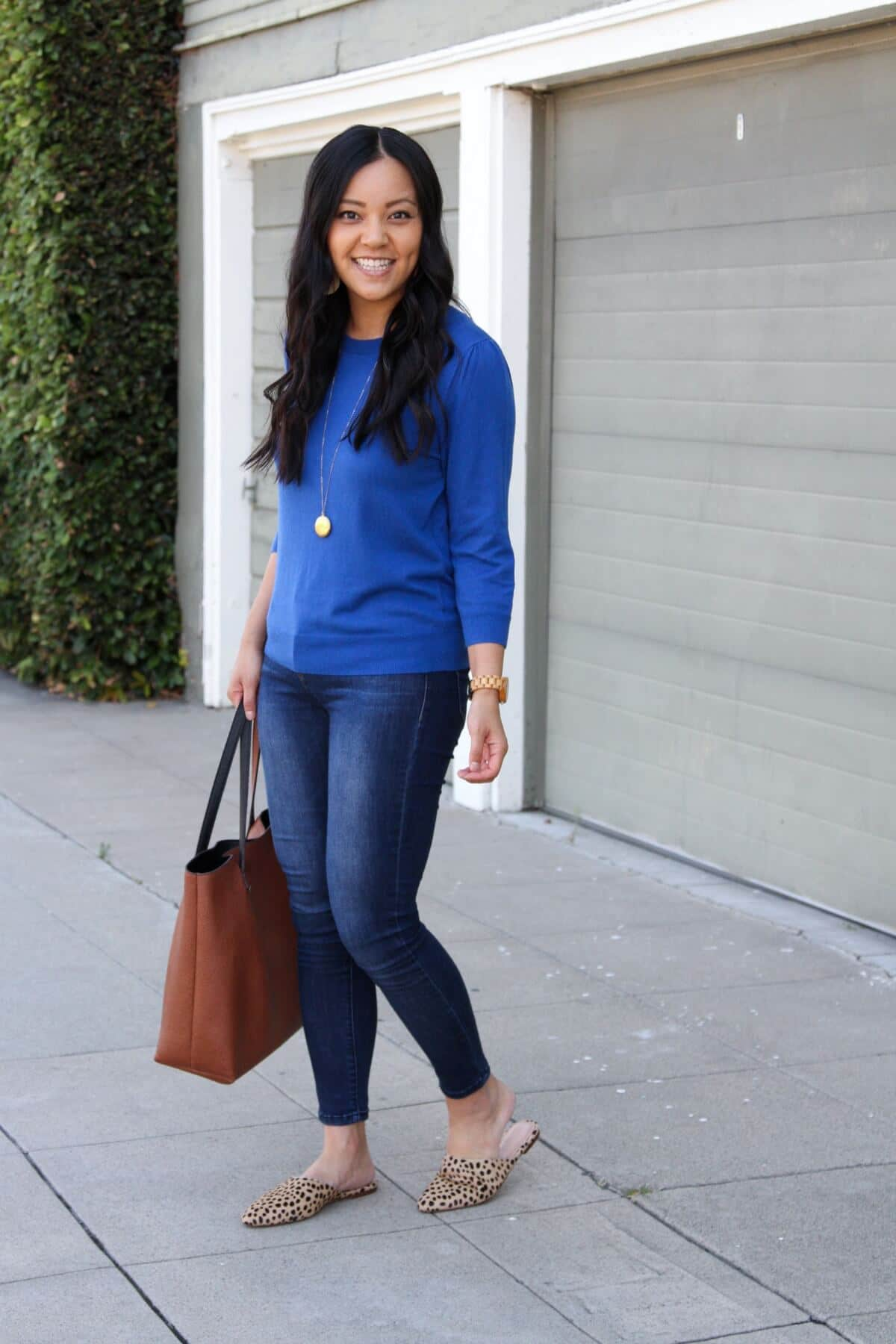 Casual Fall Outfit: blue sweater + skinny jeans + leopard mules + cognac tote + gold circle pendant necklace + gold leather earrings