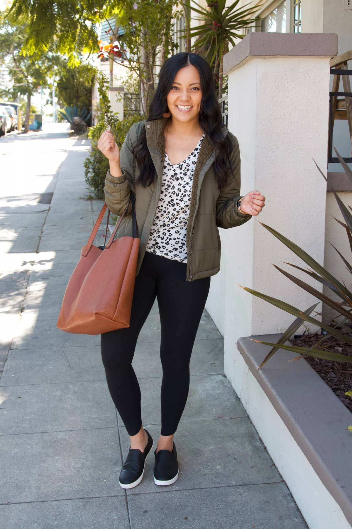 Casual Fall Outfit: leopard tee + olive quilted fleece-lined jacket + black leggings + black slip-on sneakers + cognac tote + tan leather cutout earrings