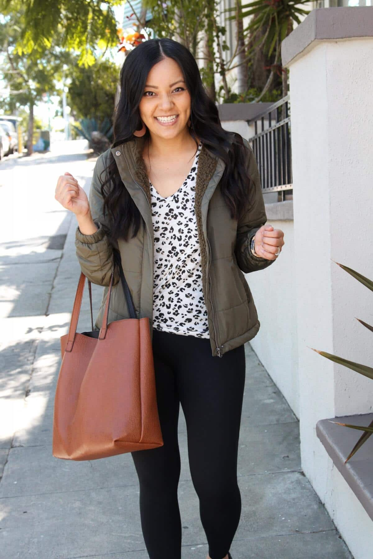 Casual Fall Outfit: olive quilted fleece-lined jacket + leopard tee + black slip-on sneakers + black leggings + tan leather cutout earrings + cognac tote
