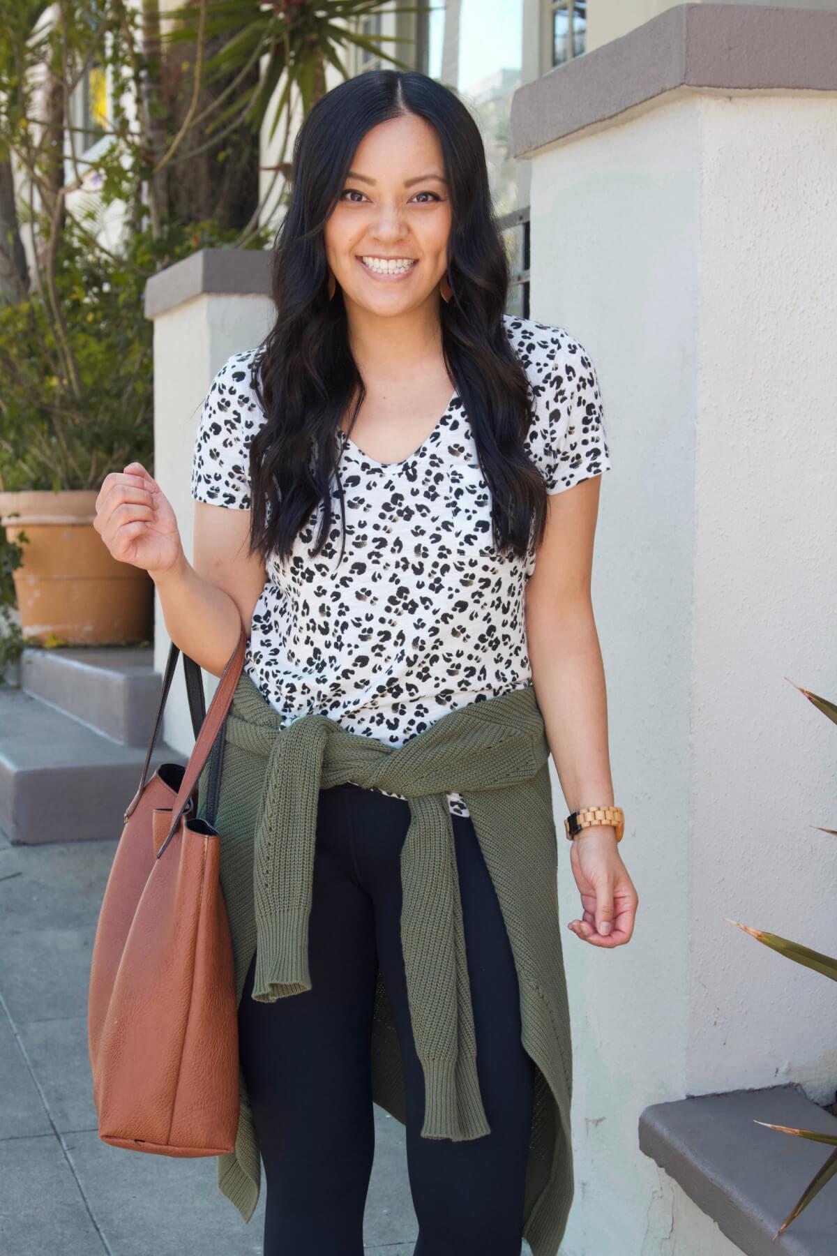 Casual Fall Outfit: olive cardigan + leopard tee + black slip-on sneakers + black leggings + cognac leather cutout earrings + cognac tote
