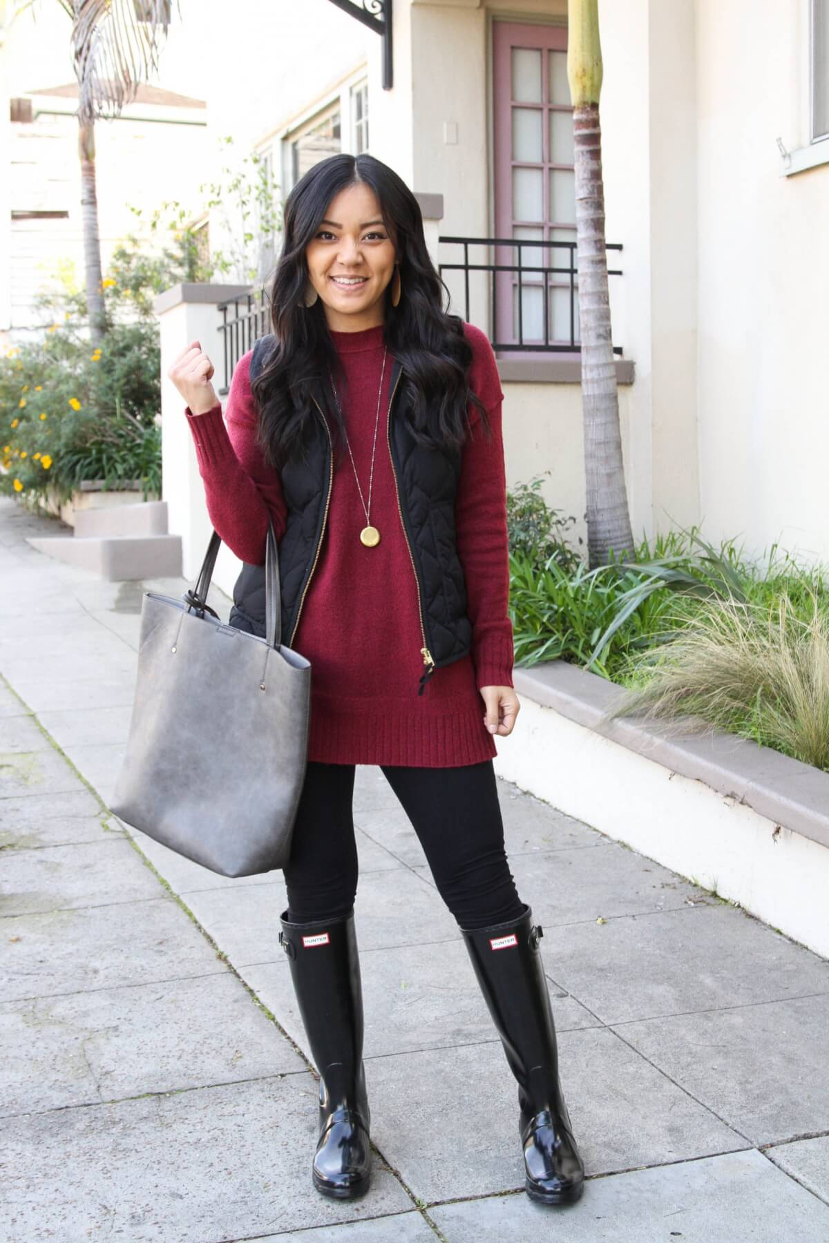 Fall Leggings Outfit: maroon tunic sweater + black quilted vest + black leggings + black hunter boots + grey tote + gold circle pendant necklace + gold leather earrings