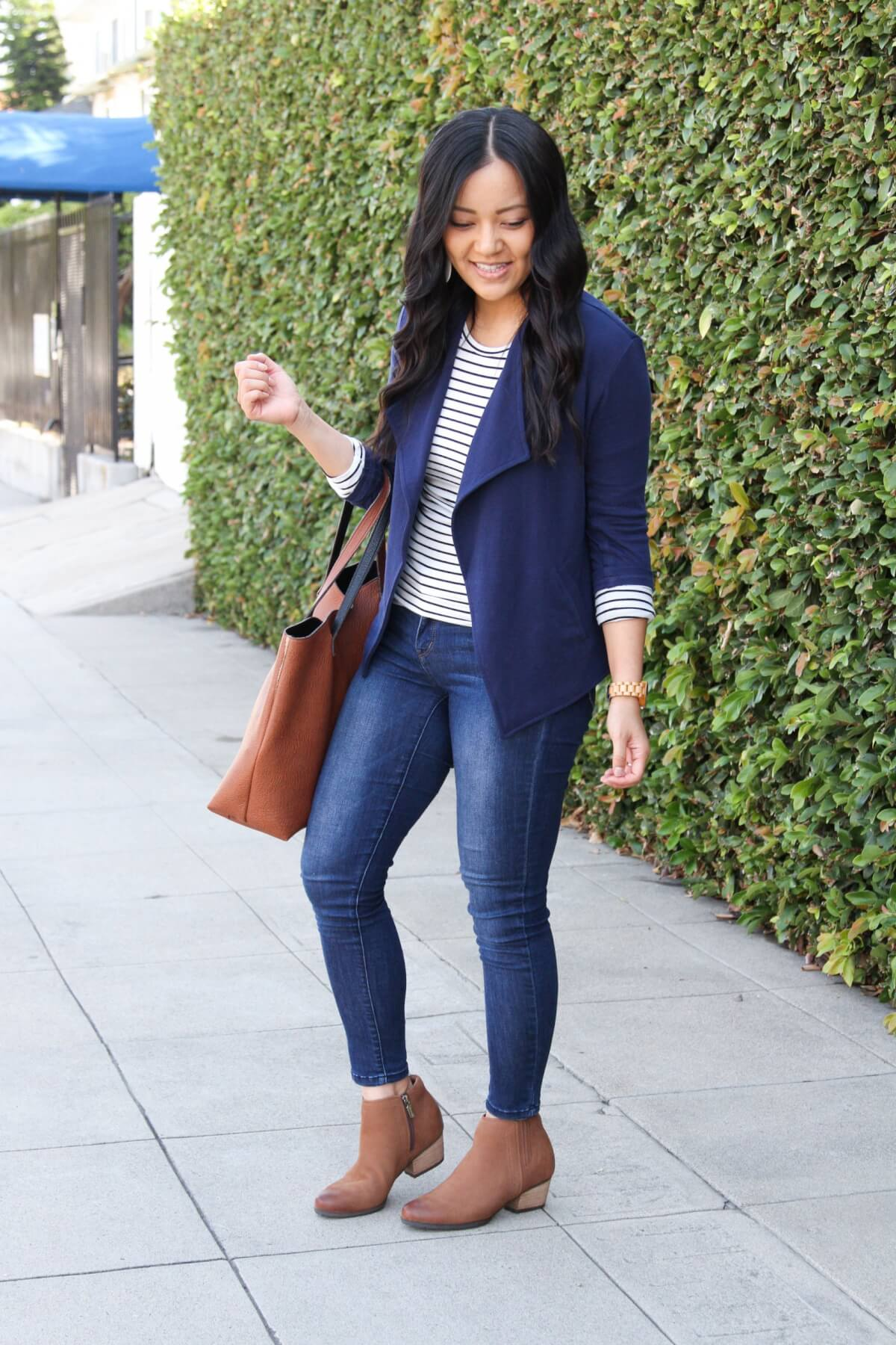 Business Casual Fall Outfit: navy knit blazer + long-sleeve striped tee + cognac booties + skinny jeans + gold leather earrings + cognac tote