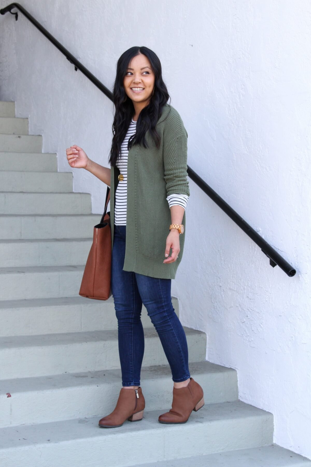 Casual Fall Outfit: olive cardigan + long sleeve striped tee + cognac booties + skinny jeans + tan cutout leather earrings + cognac tote + long gold circle pendant necklace