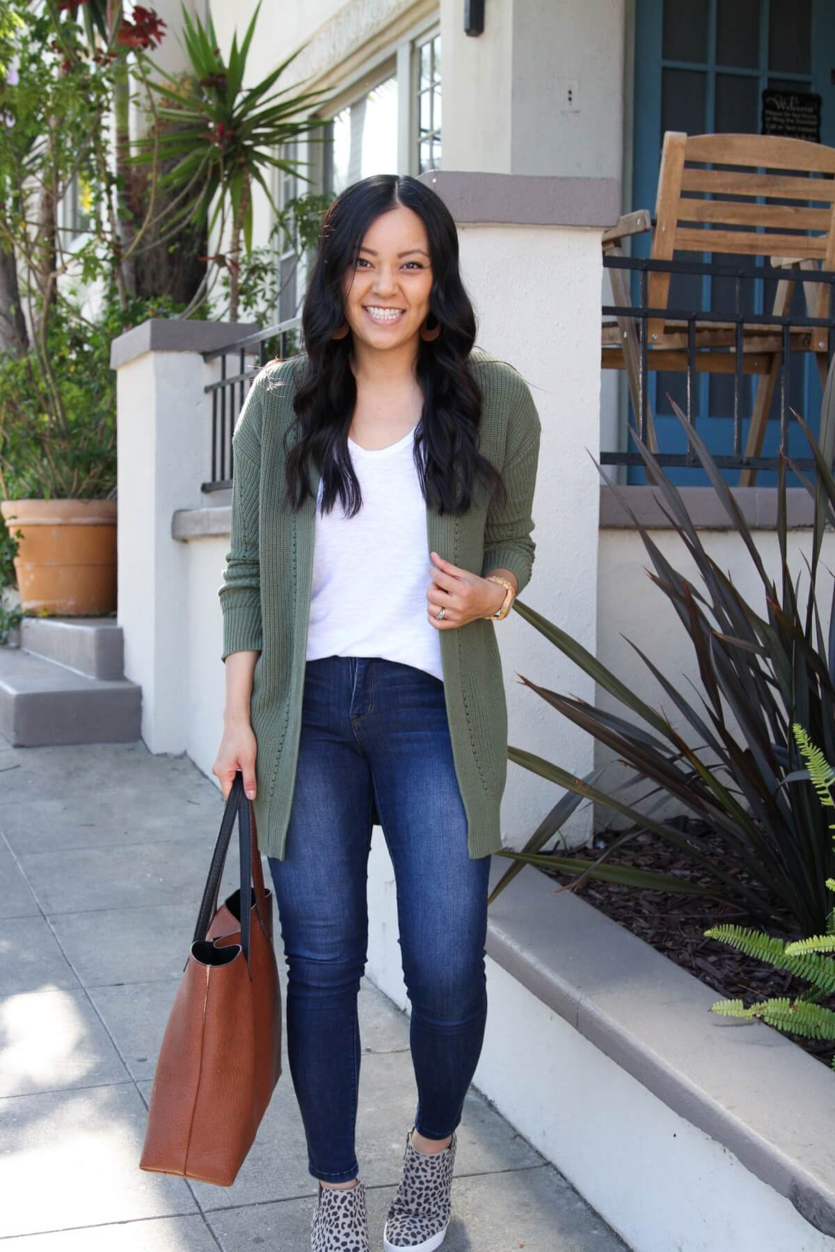 Casual Fall Outfit: olive cardigan + white tee + leopard wedge sneakers + skinny jeans + cognac leather cutout earrings + cognac tote
