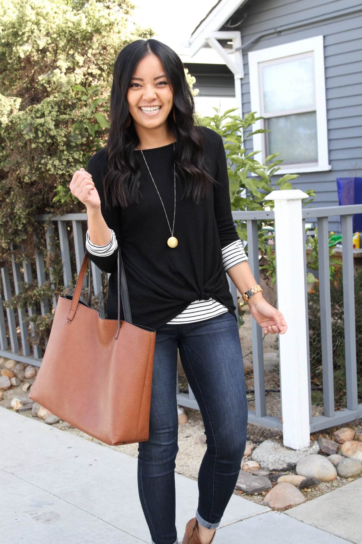 Casual Fall Outfit: long sleeve striped tee + black twist-front fleece pullover + skinny jeans + cognac booties + cognac tote + long gold circle pendant necklace + tan leather cutout earrings