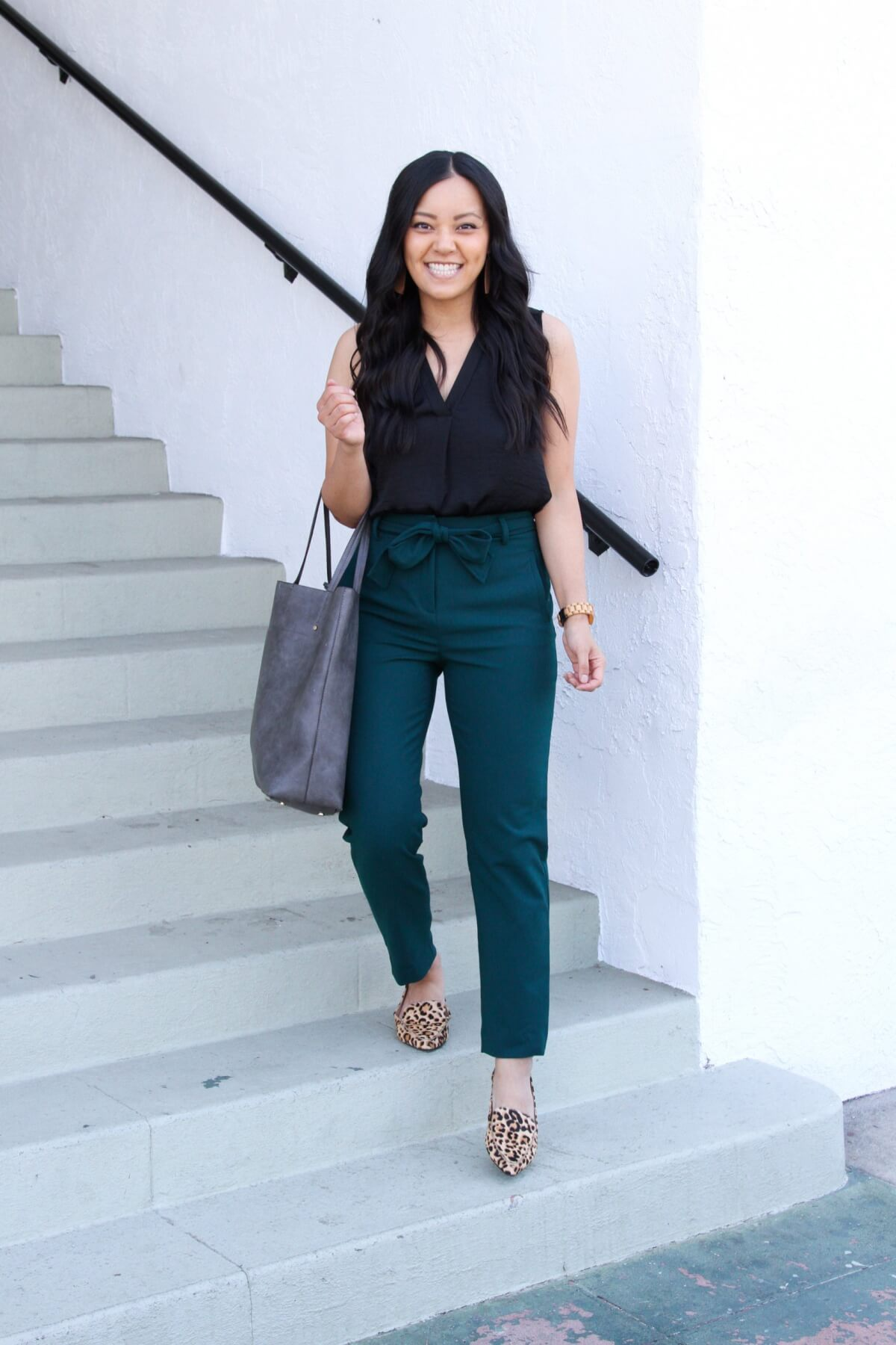 Business Casual Outfit: black sleeveless v-neck blouse + dark green tie-waist pants + leopard loafers + grey tote + tan leather earrings