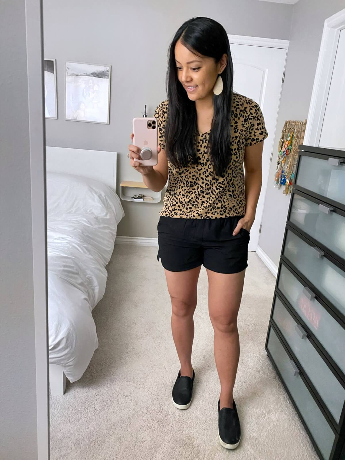 Casual Summer Outfit: leopard v-neck tee + black shorts + black slip-on sneakers + metallic leather earrings