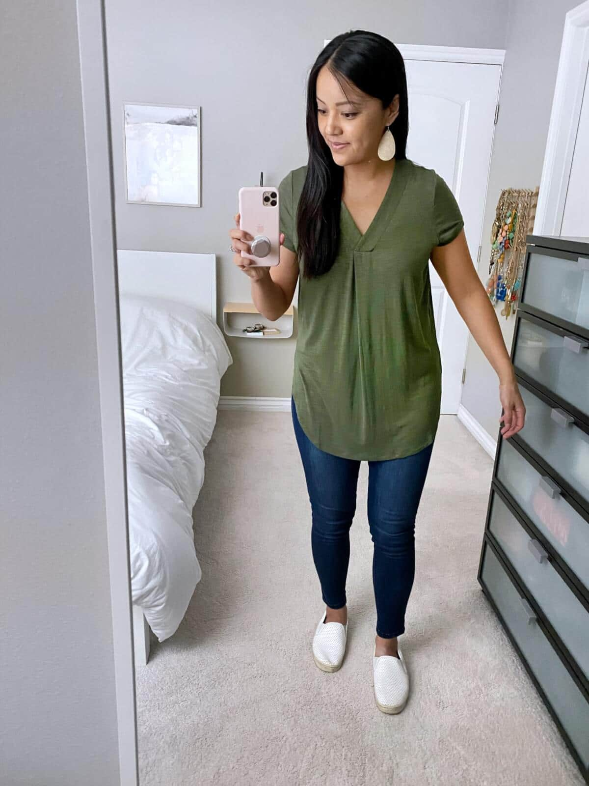 Fall Jeans Outfit: olive v-neck tunic + skinny jeans + white slip-on sneakers + metallic leather earrings