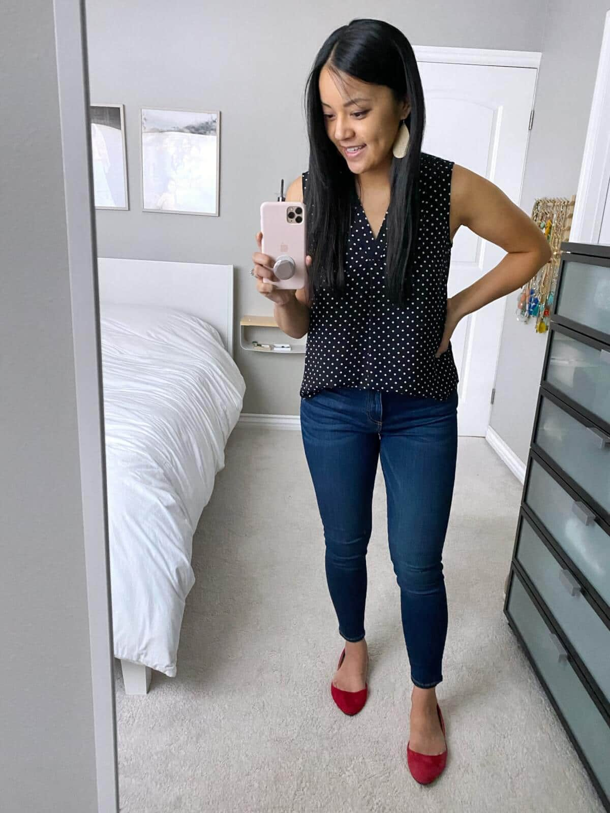 Dressy Casual Outfit: black and white dotted sleeveless blouse + skinny jeans + red flats + metallic leather earrings