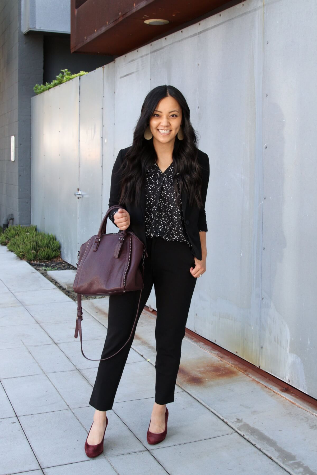 Business Casual Outfit: black printed top + black blazer + black ankle pants + maroon suede heels + maroon bag + metallic leather earrings