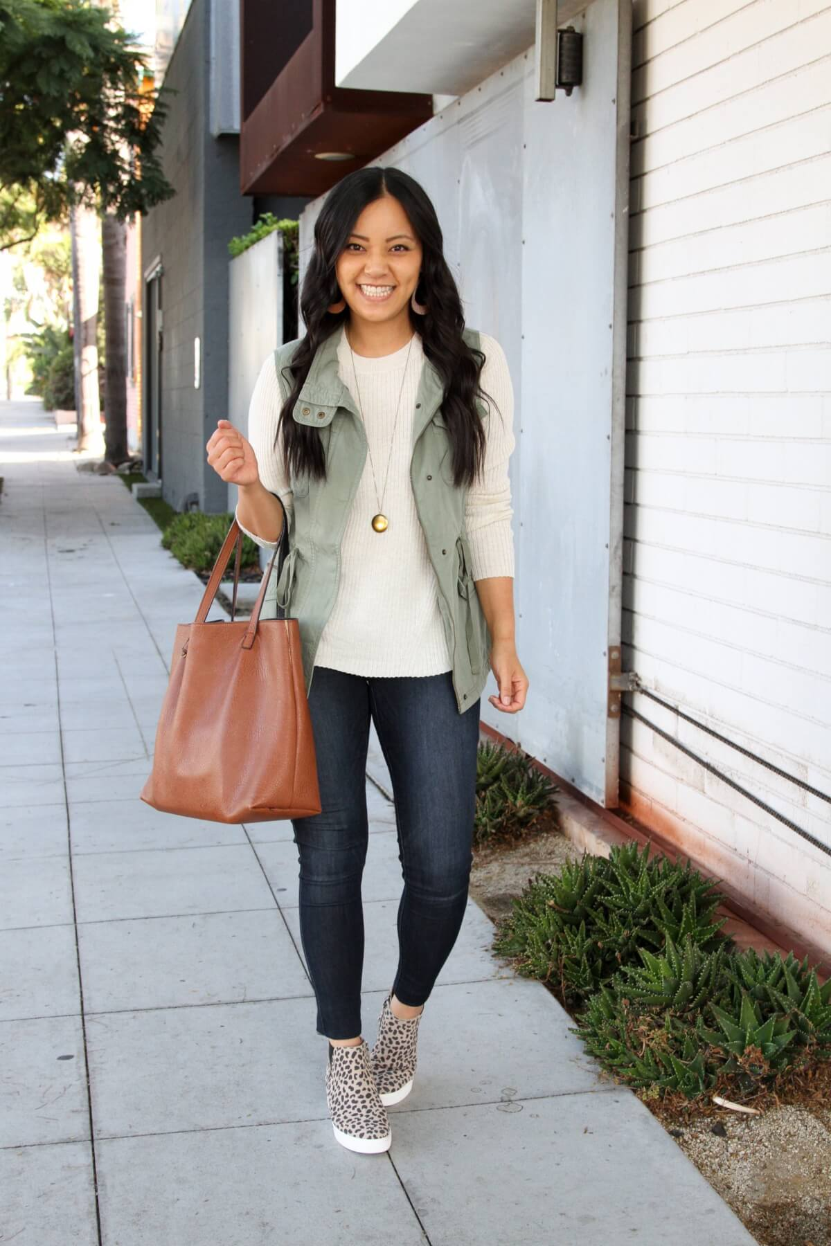 Fall Casual Outfit: cream crewneck sweater + utility vest + skinny jeans + leopard wedge sneakers + cognac tote + long gold circle pendant necklace + tan leather earrings