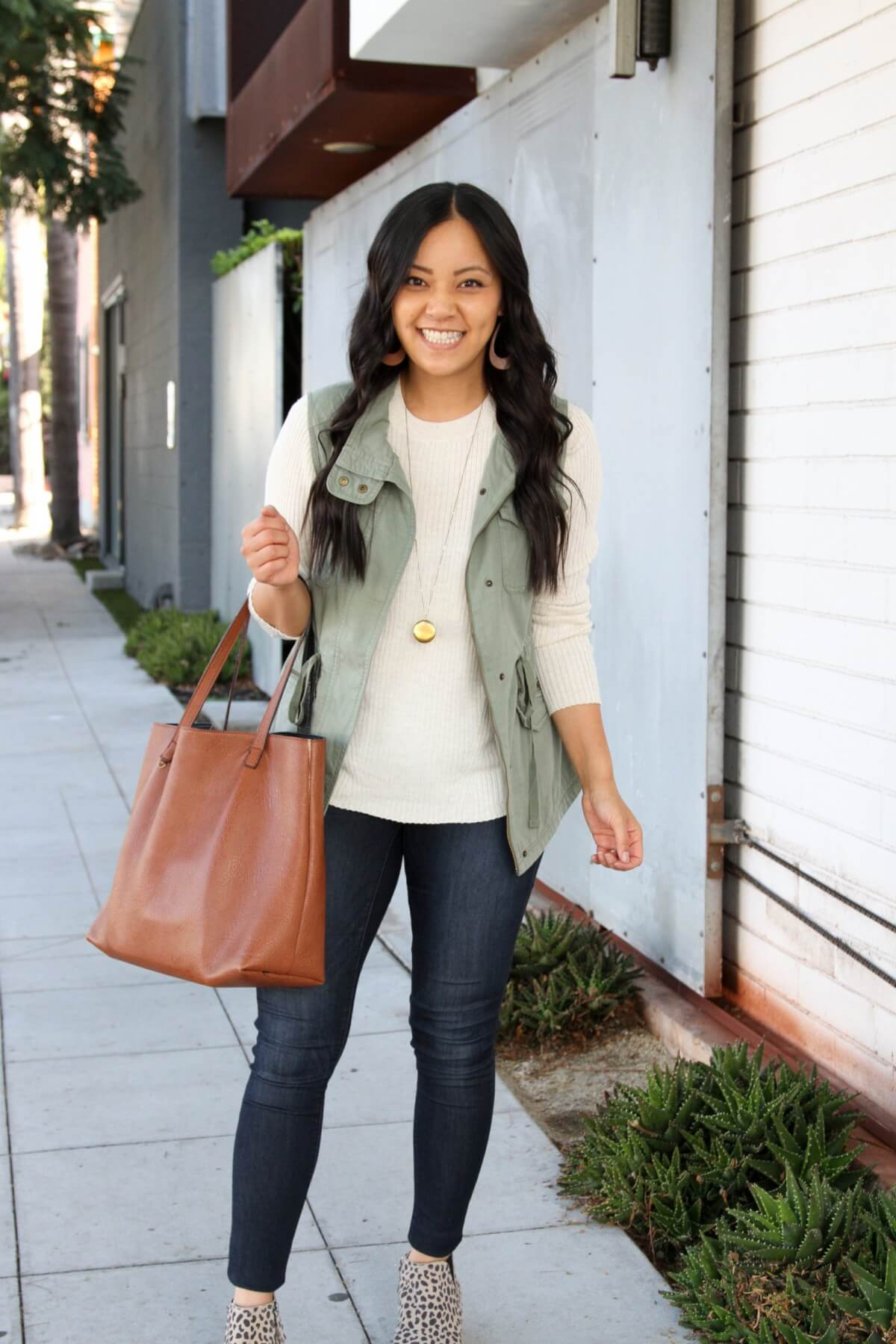 Fall Casual Outfit: utility vest + cream crewneck sweater + leopard wedge sneakers + skinny jeans + tan leather earrings + cognac tote + long gold circle pendant necklace
