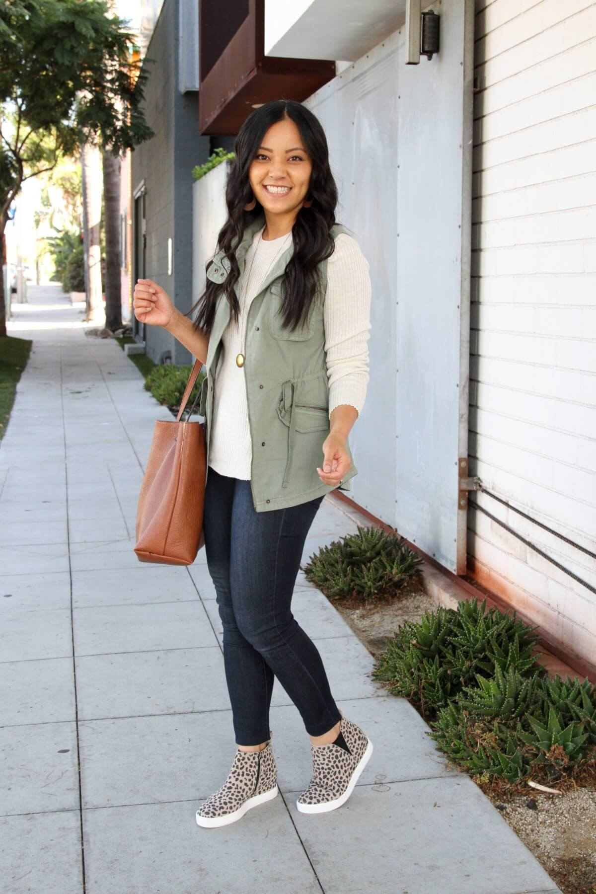 Fall Casual Outfit: cream crewneck sweater + utility vest + leopard wedge sneakers + skinny jeans + long gold circle pendant necklace + tan leather earrings + cognac tote