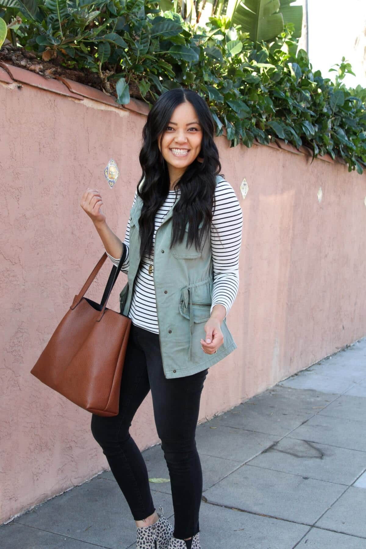 Fall Casual Outfit: utility vest + long sleeve striped tee + leopard wedge sneakers + black skinny jeans + tan leather earrings + cognac tote + long gold circle pendant necklace