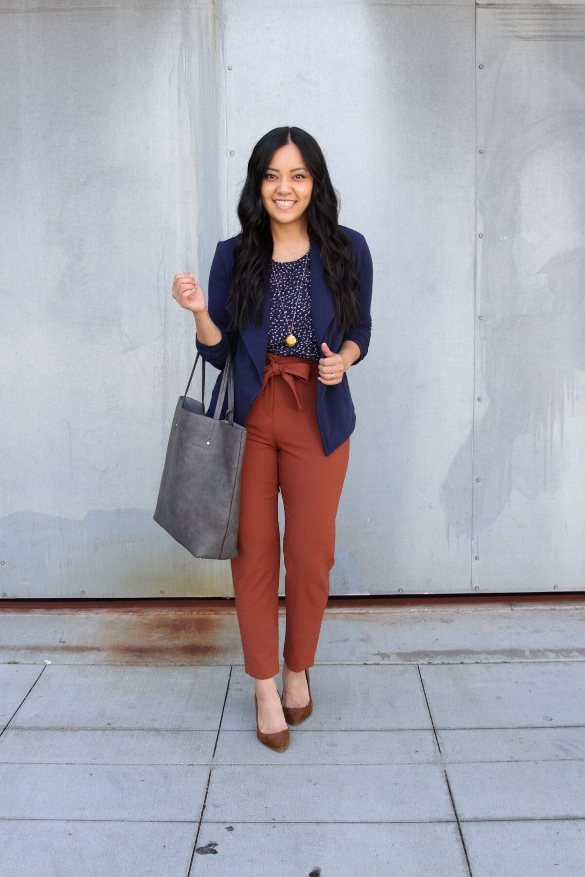 Business Casual Outfit: navy knit blazer + navy printed top + brown suede heels + rust tie waist pants + long gold circle pendant necklace + grey tote bag