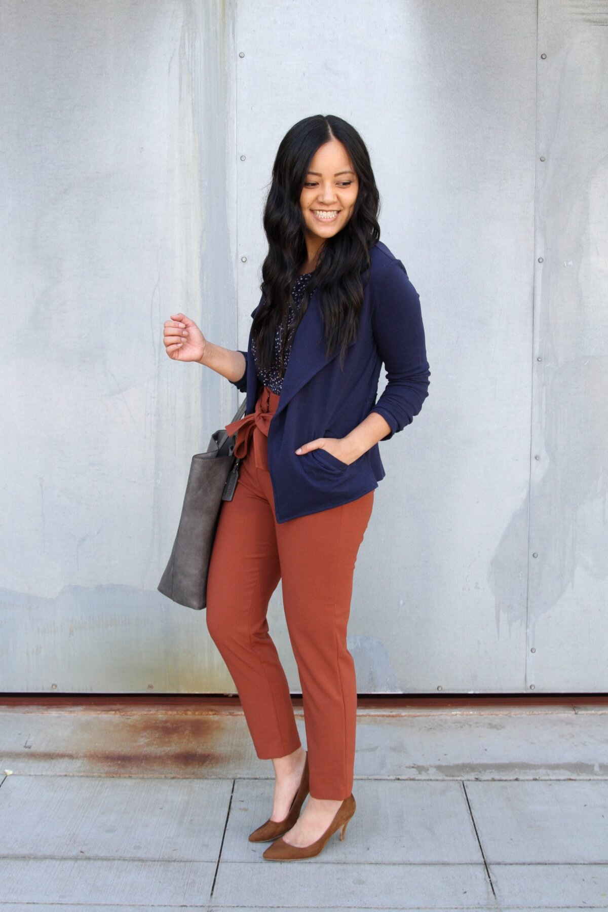 Business Casual Outfit: navy printed top + navy knit blazer + rust tie waist pants + brown suede heels + grey tote bag + long gold circle pendant necklace