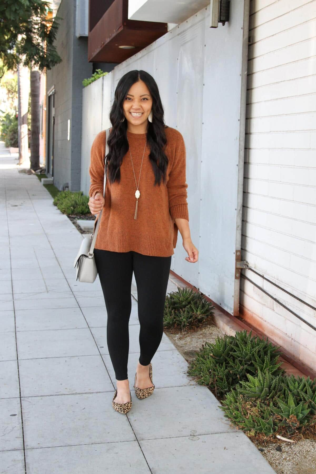 Casual Fall Outfit: black skinny pants + rust crewneck sweater + grey crossbody bag + leopard print flats + metallic leather earrings + long white and gold tassel pendant necklace