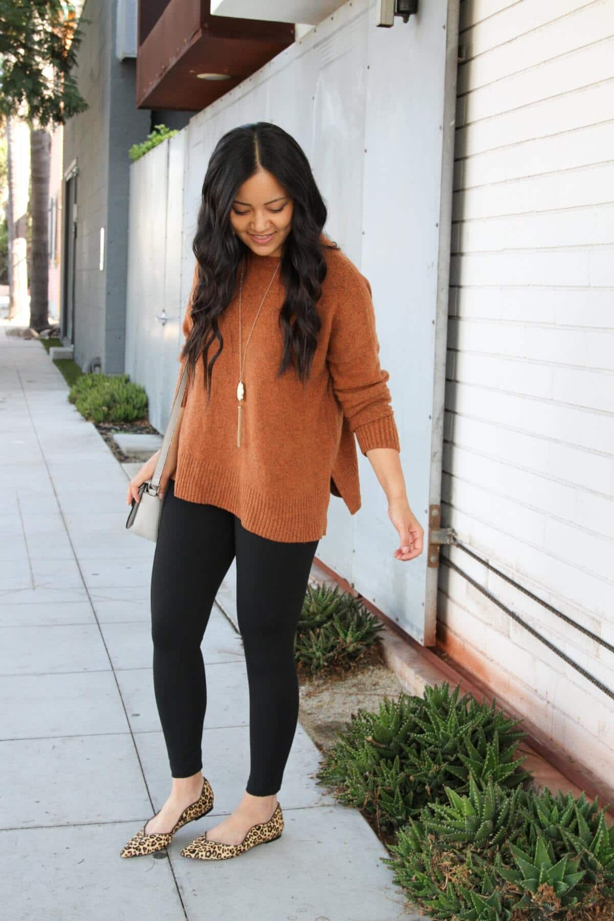Casual Fall Outfit: rust crewneck sweater + black skinny pants + leopard print flats + grey crossbody bag + long white and gold tassel pendant necklace + metallic leather earrings