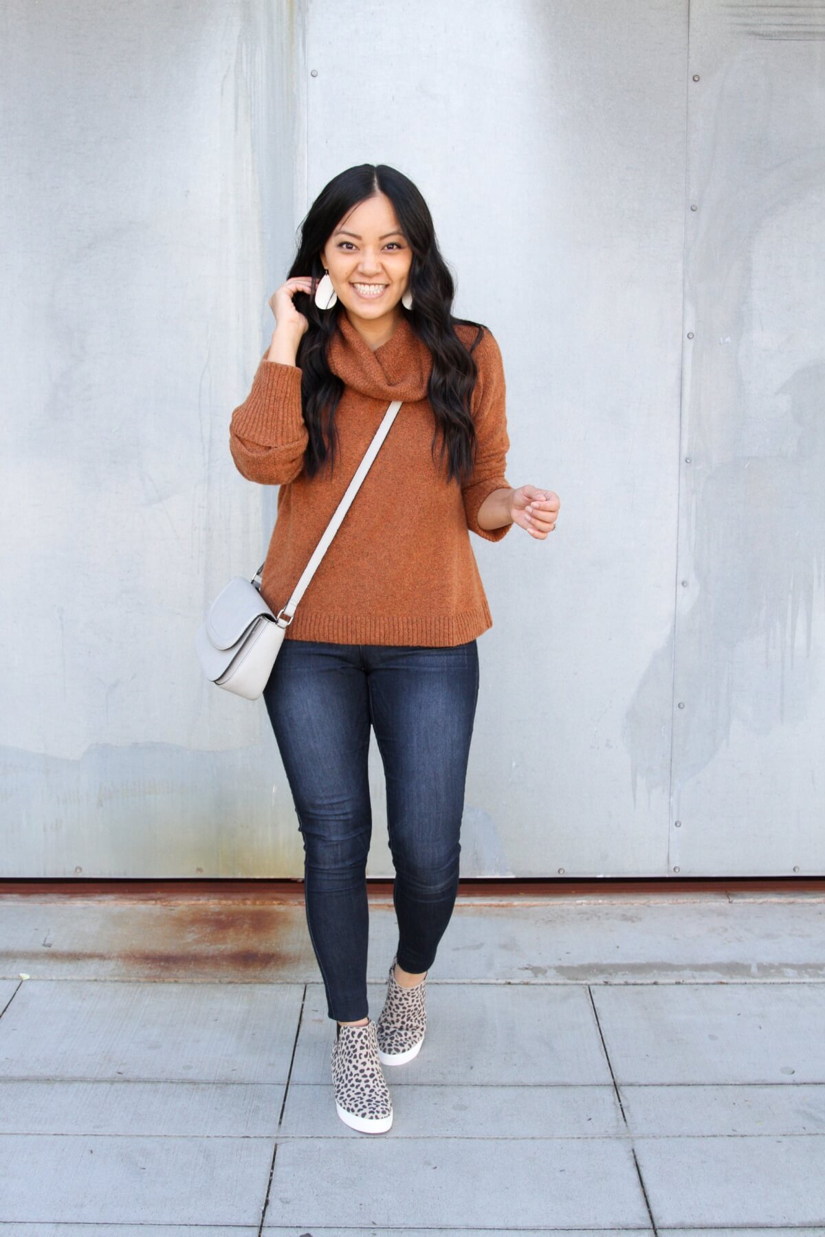 Fall Casual Outfit: rust cowl neck sweater + skinny jeans + leopard wedge sneakers + grey crossbody bag + metallic leather earrings