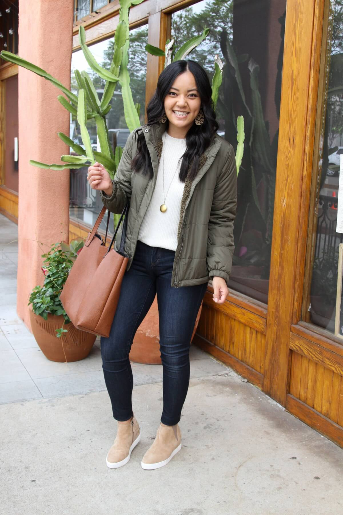 Fall Skinny Jeans Outfit: cream sweater + olive puffer jacket + skinny jeans + tan wedge sneakers + cognac tote + long gold circle pendant necklace + leopard leather earrings