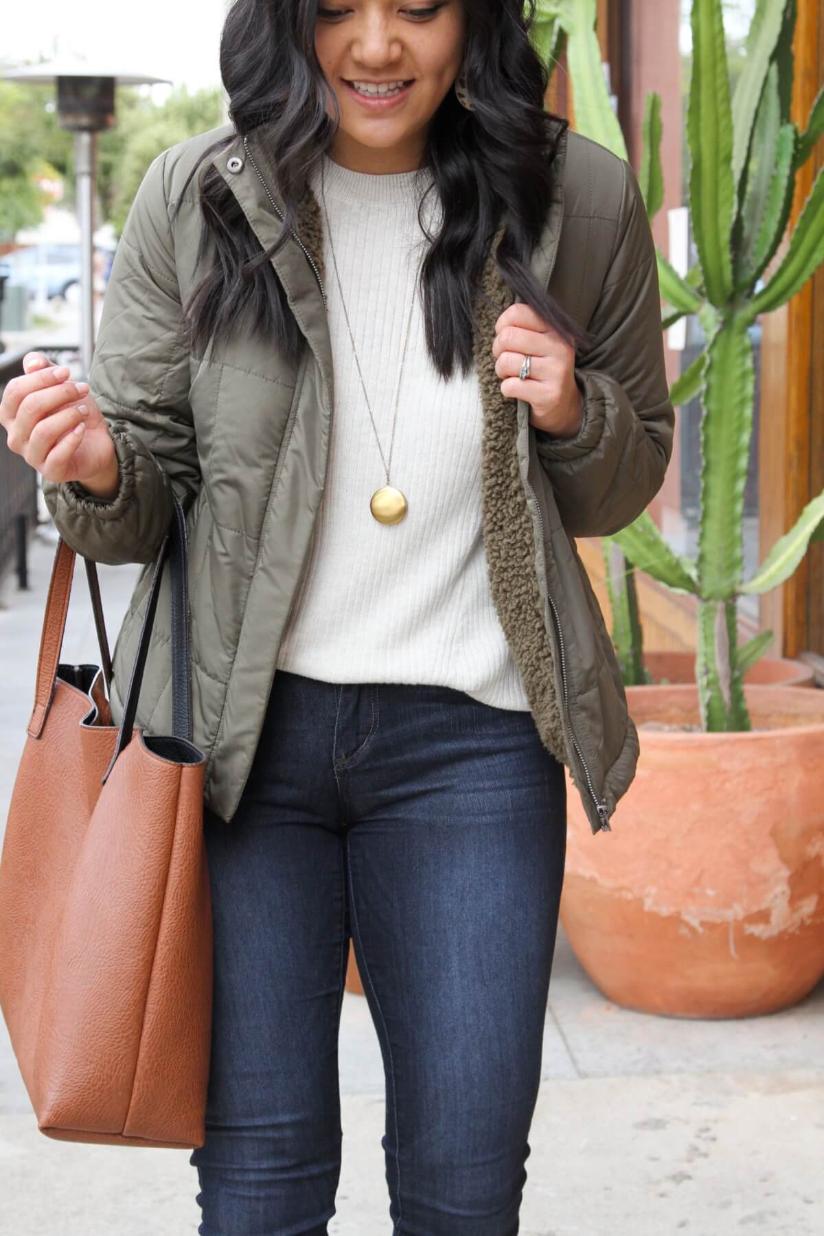 Fall Skinny Jeans Outfit: cream sweater + olive puffer jacket + tan wedge sneakers + skinny jeans + long gold circle pendant necklace + leopard leather earrings + cognac tote
