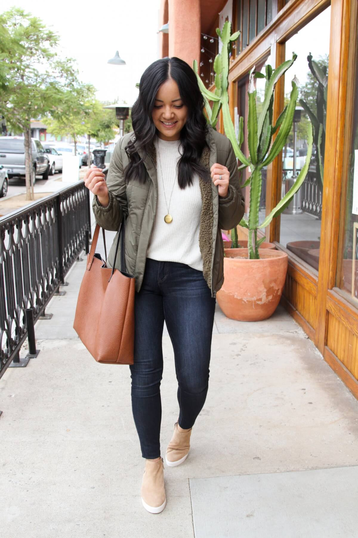 Fall Skinny Jeans Outfit: olive puffer jacket + cream sweater + tan wedge sneakers + skinny jeans + leopard leather earrings + cognac tote + long gold circle pendant necklace