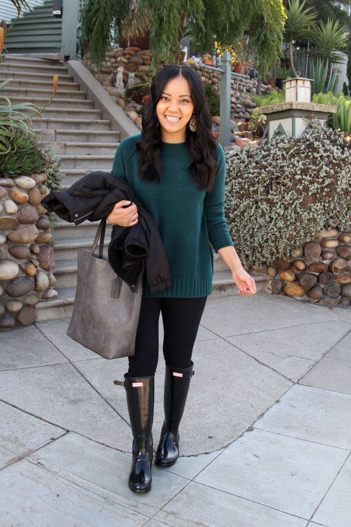 Fall Rain Boots Outfit: green crewneck sweater + black puffer jacket + black leggings + black hunter boots + grey tote + leopard print leather earrings