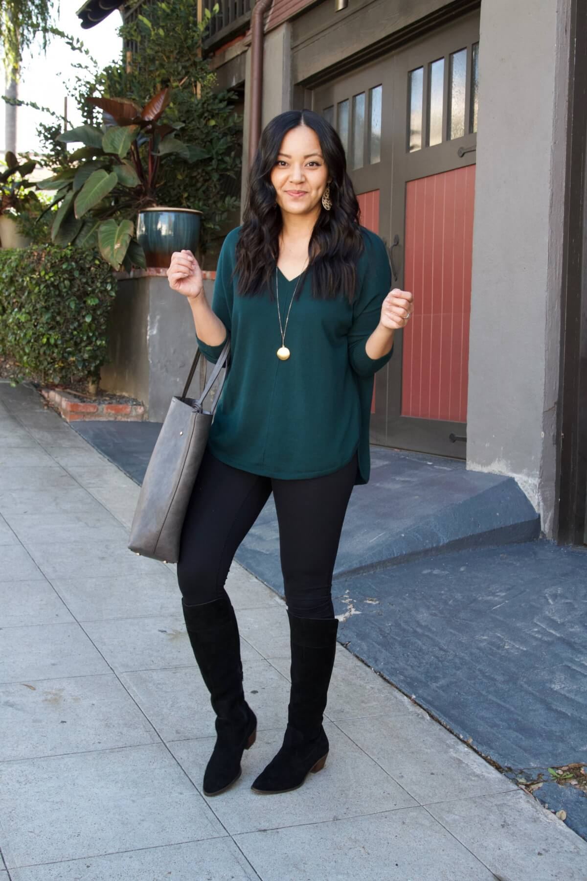 Fall Leggings Outfit: black leggings + green v-neck sweater + grey tote + black suede boots + leopard print leather earrings + gold circle pendant necklace