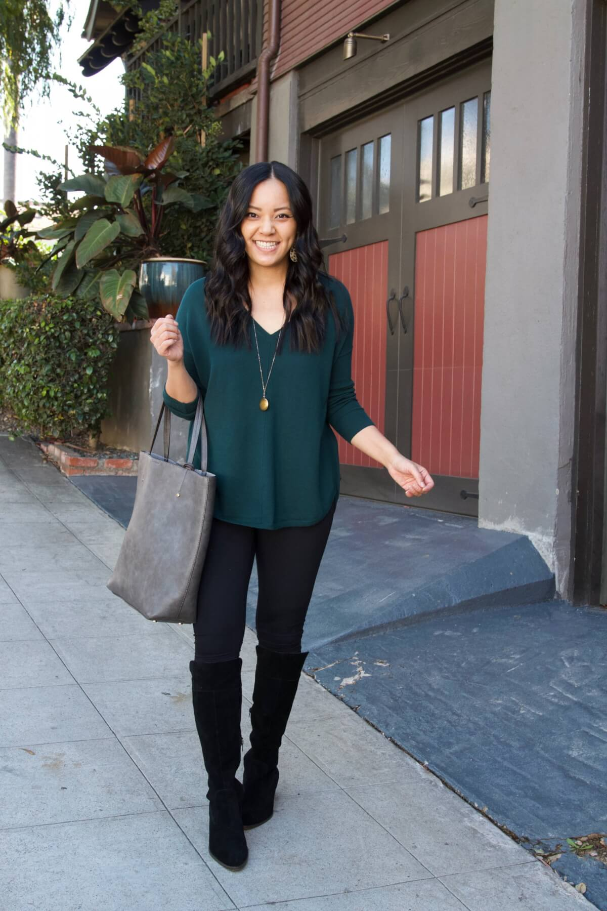 Fall Leggings Outfit: green v-neck sweater + black leggings + black suede boots + grey tote + gold circle pendant necklace + leopard print leather earrings